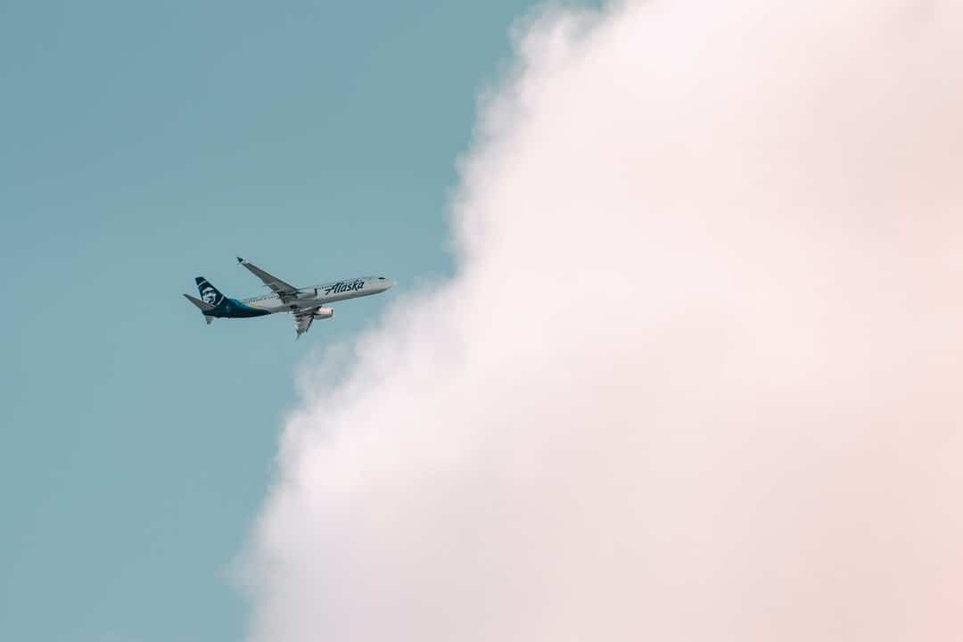 A plane flying in the air with smoke coming out of it
