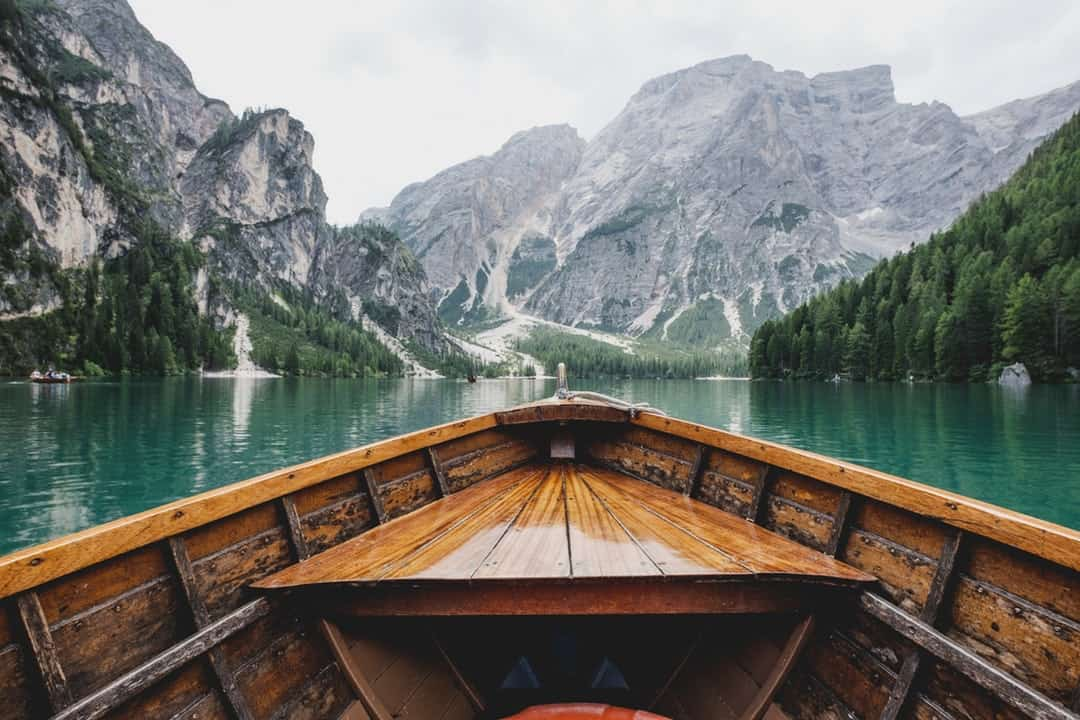 A wooden boat in a body of water with a mountain in the background